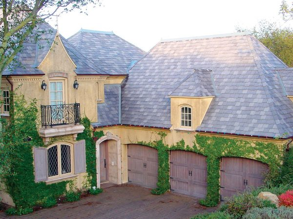 Castle style home with three carriage house doors