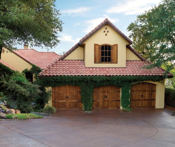 Three wood carriage house doors of Mediterranean style property