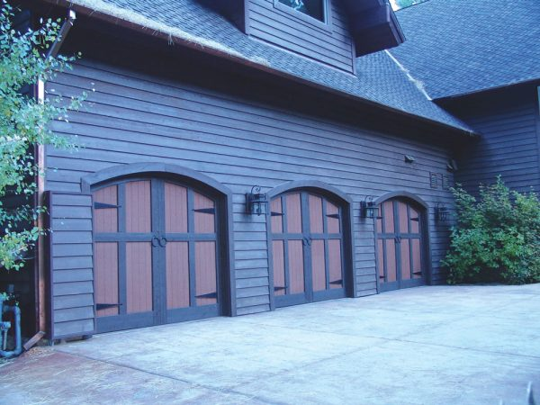 three wood and metal arched carriage house doors