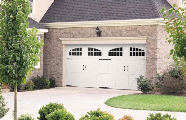 brick house with 2 white garage door