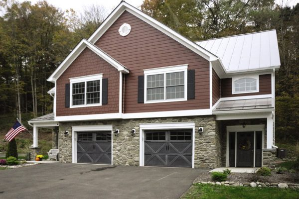 2 story house with brown sidings and stone wall