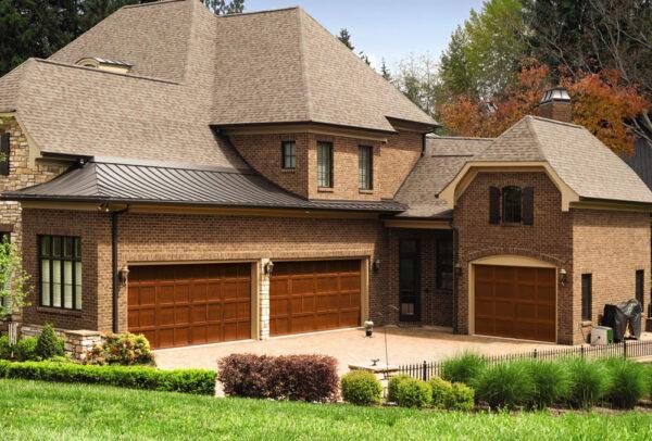 2 Story brick house with 3 brown garage doors