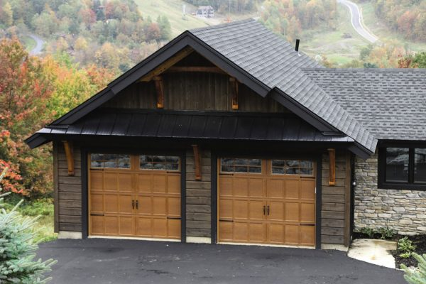 wooden siding stone house with 2 garage doors