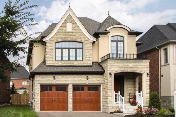 2 story white house with 2 brown wooden garage doors