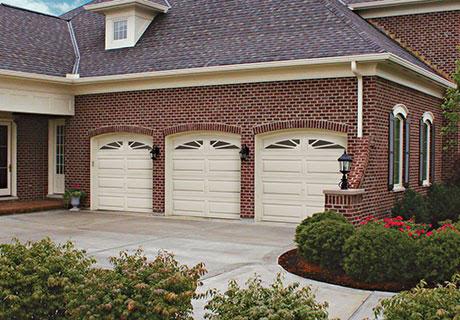 white garage doors of a brick house