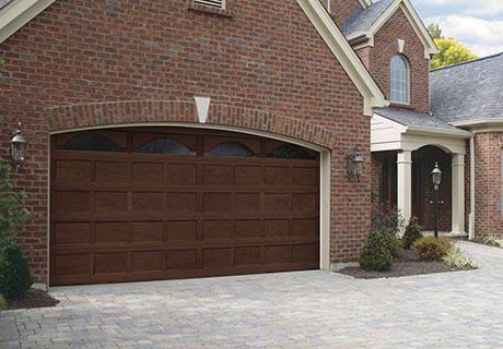 large wooden garage door of a brick house