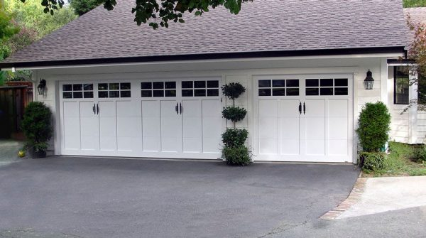 three sets of white carriage house garage doors