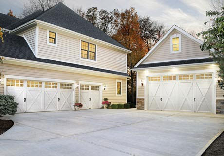 house exterior with multiple white garage doors