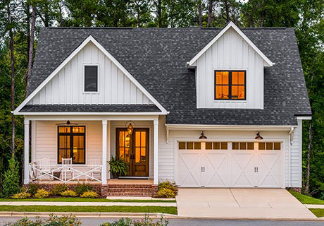 white country style home with garage doors