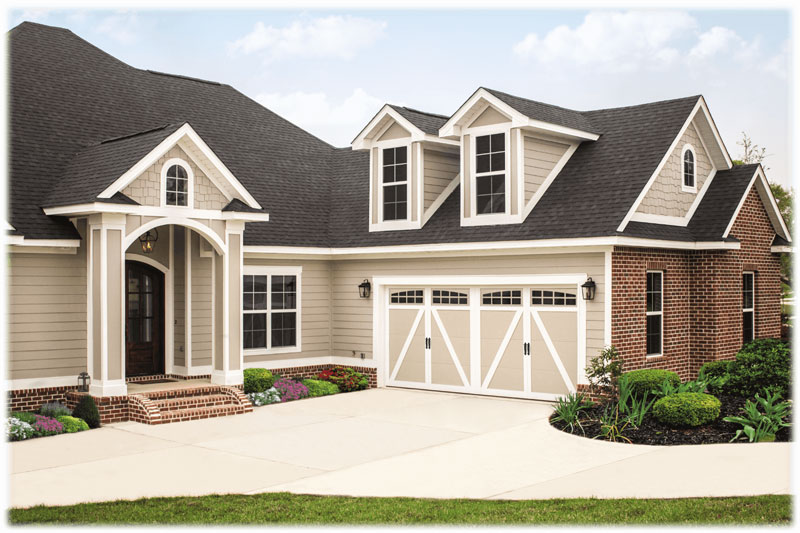 white house with brick sides and 2 white garage doors