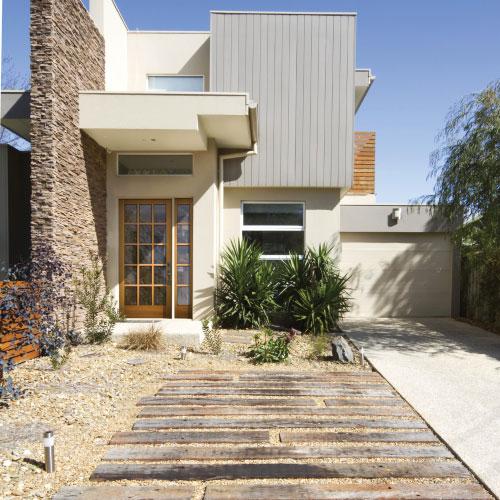 small house with single garage door and wood frame glass door