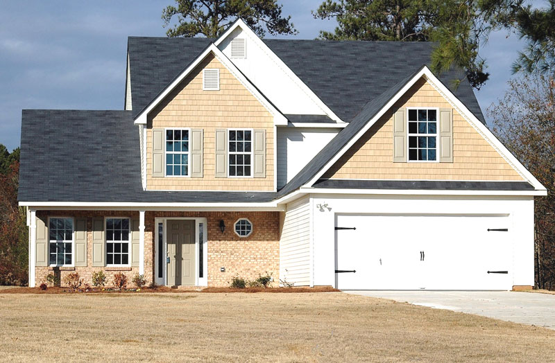 cream colored house with white accents and wide white garage door