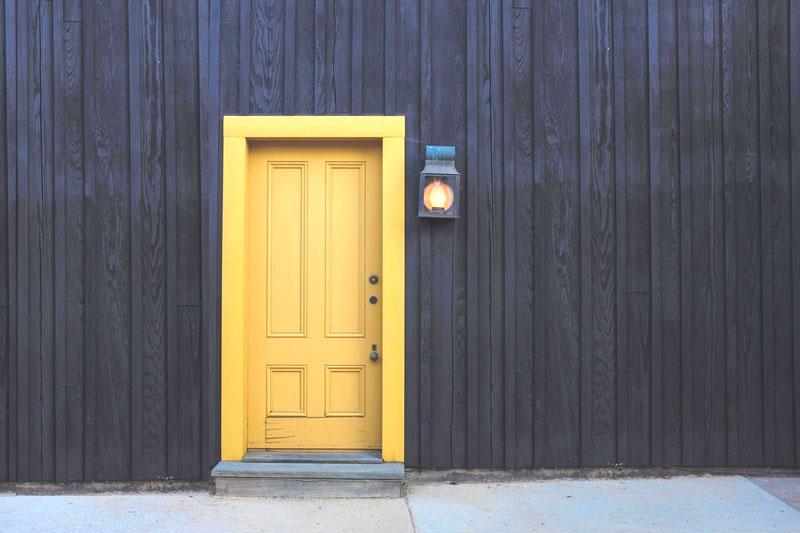 dark brown vertical wood sidings yellow door and lamp
