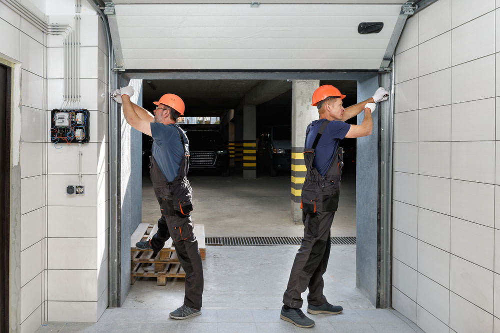 Workers are installing lifting gates of the garage