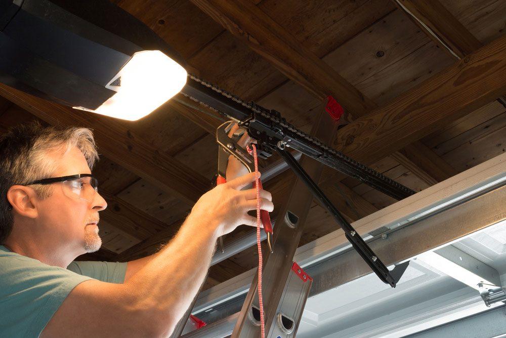 man installing automatic garage door opener
